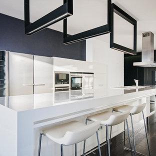 Свежая идея для дизайна: кухня в современном стиле с плоскими фасадами, белыми фасадами, белым фартуком, техникой из нержавеющей стали, островом и черным полом - отличное фото интерьера