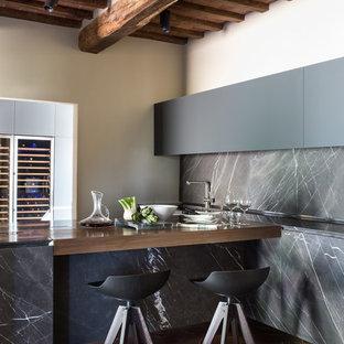 Diseño de cocina lineal, contemporánea, de tamaño medio, abierta, con armarios con paneles lisos, puertas de armario grises, encimera de mármol, salpicadero verde, salpicadero de losas de piedra, suelo de ladrillo y península