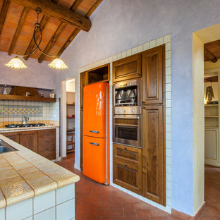Photo of a mediterranean u-shaped kitchen in Florence with a drop-in sink, raised-panel cabinets, dark wood cabinets, multi-coloured splashback, coloured appliances, brick floors, no island, red floor and yellow benchtop.