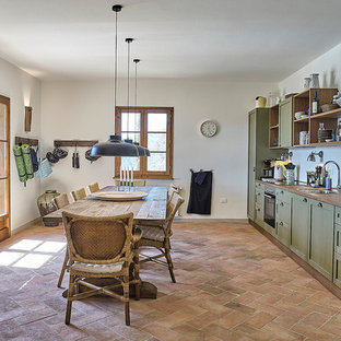Large country single-wall eat-in kitchen in Florence with raised-panel cabinets, green cabinets, wood benchtops, white splashback, stainless steel appliances, brick floors, no island and red floor.