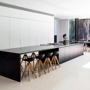 Ejemplo de cocina comedor de galera, moderna, extra grande, con fregadero bajoencimera, armarios con paneles lisos, puertas de armario blancas y una isla
