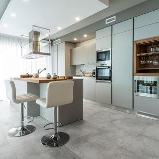 Foto di una cucina parallela eclettica con pavimento in gres porcellanato, pavimento grigio, ante lisce, ante grigie, top in legno, paraspruzzi grigio, elettrodomestici da incasso, isola e top marrone
