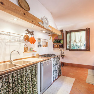 This is an example of a mediterranean single-wall separate kitchen in Catania-Palermo with stainless steel appliances, no island, a drop-in sink, recessed-panel cabinets, light wood cabinets, wood benchtops, white splashback, brick floors, brown floor and beige benchtop.
