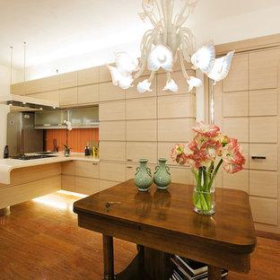 Esempio di una grande cucina design con ante lisce, ante in legno chiaro, elettrodomestici in acciaio inossidabile e una penisola