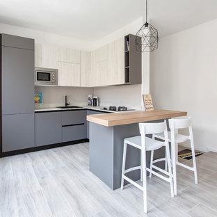 Ispirazione per una cucina ad U design di medie dimensioni e chiusa con ante lisce, ante grigie, elettrodomestici in acciaio inossidabile, penisola, lavello da incasso, paraspruzzi beige e top bianco