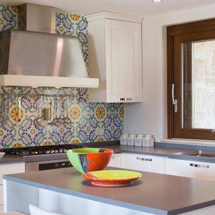 Esempio di una piccola cucina a L design con lavello a doppia vasca, ante lisce, ante bianche, paraspruzzi multicolore, paraspruzzi con piastrelle a mosaico, elettrodomestici in acciaio inossidabile, isola e top grigio