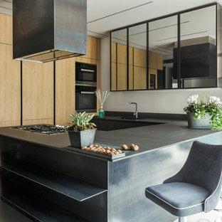 Ispirazione per una cucina ad U industriale di medie dimensioni con ante lisce, ante in legno scuro, penisola e top nero