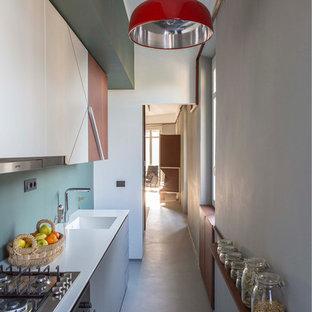 Foto di una piccola cucina lineare moderna chiusa con lavello integrato, ante lisce, ante bianche e top in superficie solida