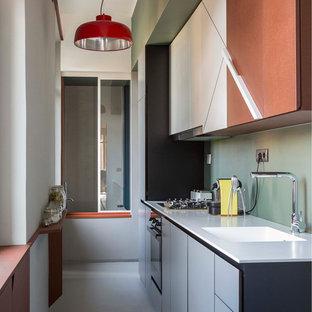 Foto di una cucina lineare minimalista chiusa e di medie dimensioni con ante lisce, paraspruzzi verde, nessuna isola, pavimento grigio e top bianco