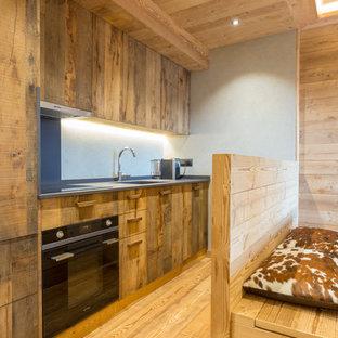 Idee per una cucina rustica con pavimento in legno massello medio, nessuna isola, ante lisce, ante in legno bruno, pavimento marrone e top grigio