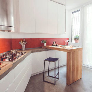 Inspiration for a mid-sized contemporary single-wall eat-in kitchen in Rome with flat-panel cabinets, white cabinets, concrete benchtops, red splashback and porcelain floors.