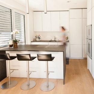 Esempio di una cucina contemporanea di medie dimensioni con lavello sottopiano, ante lisce, ante bianche, top in superficie solida, paraspruzzi bianco, elettrodomestici in acciaio inossidabile, parquet chiaro e penisola