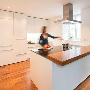 Foto di una cucina design di medie dimensioni con lavello sottopiano, ante lisce, ante bianche, top in superficie solida, paraspruzzi bianco, elettrodomestici in acciaio inossidabile, pavimento in legno massello medio e isola