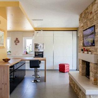 Esempio di una cucina contemporanea con elettrodomestici in acciaio inossidabile, penisola, pavimento grigio, ante lisce, ante bianche, paraspruzzi bianco e top bianco