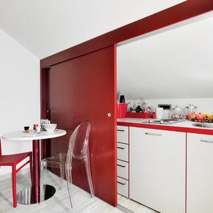 Bild på ett avskilt, litet funkis linjärt kök, med en nedsänkt diskho, släta luckor, vita skåp, laminatbänkskiva, klinkergolv i porslin, vitt stänkskydd och grått golv