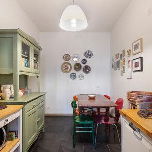 他の地域の中サイズのエクレクティックスタイルのおしゃれなキッチン (ダブルシンク、落し込みパネル扉のキャビネット、白いキャビネット、木材カウンター、黄色いキッチンパネル、セラミックタイルのキッチンパネル、シルバーの調理設備の、磁器タイルの床、アイランドなし、黒い床、茶色いキッチンカウンター) の写真