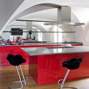 Ispirazione per un cucina con isola centrale contemporaneo con lavello sottopiano, ante lisce, ante rosse, paraspruzzi a specchio, parquet chiaro e top grigio