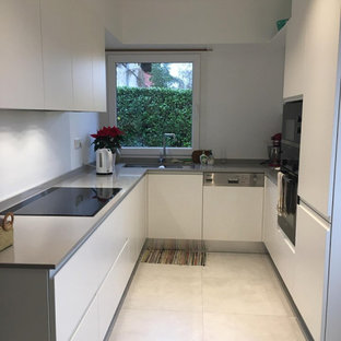 Photo of a small modern u-shaped separate kitchen in Other with a double-bowl sink, flat-panel cabinets, white cabinets, zinc benchtops, beige splashback, glass sheet splashback, stainless steel appliances, porcelain floors, no island, multi-coloured floor, grey benchtop and coffered.