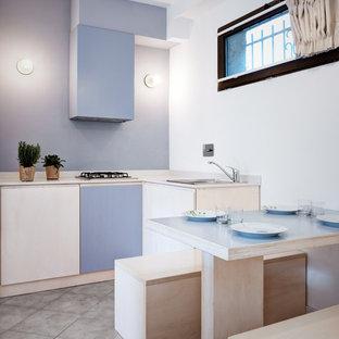 Ispirazione per una piccola cucina stile marinaro con ante lisce, pavimento grigio, top bianco, ante blu, paraspruzzi blu, lavello da incasso e nessuna isola