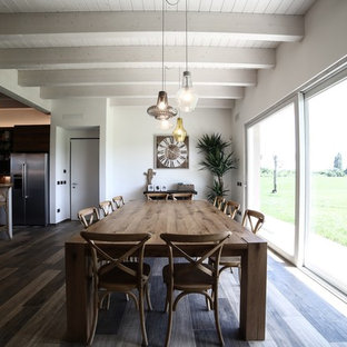 Large industrial u-shaped kitchen/diner in Bologna with a double-bowl sink, louvered cabinets, distressed cabinets, concrete worktops, multi-coloured splashback, cement tile splashback, stainless steel appliances, porcelain flooring, an island, multi-coloured floors and grey worktops.