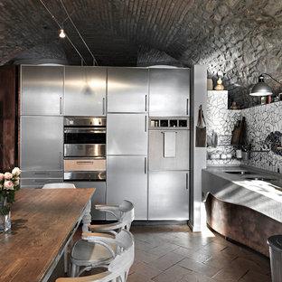 他の地域のインダストリアルスタイルのおしゃれなL型キッチン (ダブルシンク、ステンレスキャビネット、フラットパネル扉のキャビネット、モザイクタイルのキッチンパネル、シルバーの調理設備の、レンガの床、アイランドなし、茶色い床、グレーのキッチンカウンター) の写真