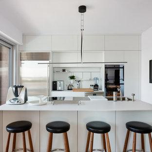 Idee per un grande cucina con isola centrale con ante lisce, paraspruzzi bianco, elettrodomestici in acciaio inossidabile, top bianco, lavello sottopiano, ante bianche e pavimento in legno massello medio