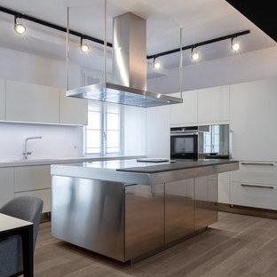 Ispirazione per una grande cucina minimal con lavello sottopiano, ante lisce, ante bianche, paraspruzzi bianco, parquet chiaro, isola, top in acciaio inossidabile, elettrodomestici da incasso, pavimento marrone e top grigio