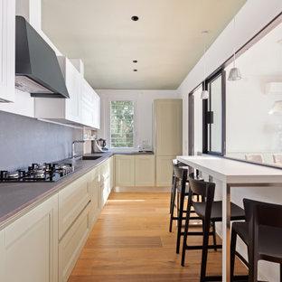 Ispirazione per una cucina a L design chiusa e di medie dimensioni con lavello integrato, ante verdi, top in superficie solida, paraspruzzi grigio, pavimento in gres porcellanato, pavimento marrone, top grigio, ante con riquadro incassato, elettrodomestici da incasso e nessuna isola