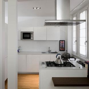 Idee per una cucina ad U design di medie dimensioni con lavello a vasca singola, ante lisce, ante bianche, top in quarzite, paraspruzzi bianco, elettrodomestici in acciaio inossidabile, penisola e pavimento in legno massello medio