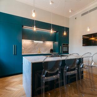 Foto di una cucina contemporanea con ante lisce, ante blu, paraspruzzi bianco, elettrodomestici in acciaio inossidabile e top bianco