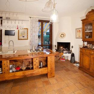 Kleine Landhausstil Wohnküche in L-Form mit Einbauwaschbecken, flächenbündigen Schrankfronten, hellen Holzschränken, Arbeitsplatte aus Holz, weißen Elektrogeräten, Terrakottaboden und Kücheninsel in Mailand
