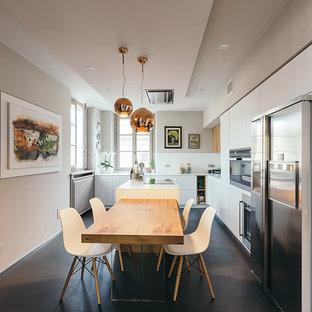 Foto di una cucina contemporanea con ante lisce, ante bianche, paraspruzzi bianco, elettrodomestici in acciaio inossidabile, pavimento nero e top bianco