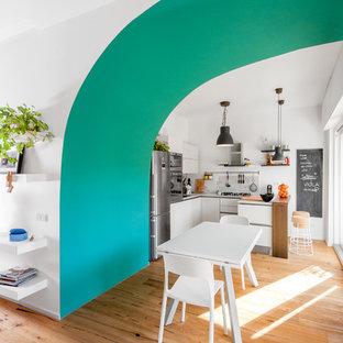 Idee per una piccola cucina minimal con penisola, ante lisce, ante bianche, elettrodomestici in acciaio inossidabile e parquet chiaro