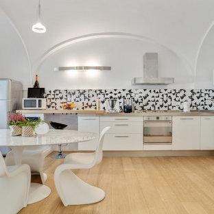 Immagine di una cucina design con ante lisce, ante bianche, paraspruzzi multicolore, elettrodomestici in acciaio inossidabile, parquet chiaro, nessuna isola, pavimento beige, top grigio e soffitto a volta