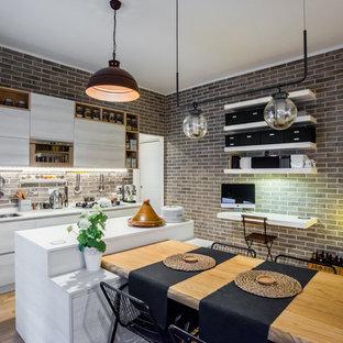 Ispirazione per una cucina industriale di medie dimensioni con top in marmo, elettrodomestici in acciaio inossidabile, isola, lavello sottopiano, ante lisce, ante bianche, paraspruzzi in mattoni, parquet chiaro e pavimento beige