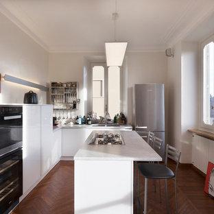 Immagine di una cucina a L minimal di medie dimensioni con ante lisce, ante bianche, top in marmo, isola, lavello a doppia vasca, elettrodomestici neri e pavimento in legno massello medio
