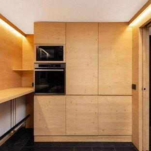 他の地域の大きいモダンスタイルのおしゃれなコの字型キッチン (ドロップインシンク、フラットパネル扉のキャビネット、淡色木目調キャビネット、大理石カウンター、マルチカラーのキッチンパネル、ガラス板のキッチンパネル、パネルと同色の調理設備、大理石の床、黒い床、黒いキッチンカウンター) の写真