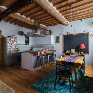 Foto di un'ampia cucina bohémian con pavimento marrone, ante lisce, ante bianche, elettrodomestici in acciaio inossidabile, pavimento in legno massello medio, penisola e top grigio