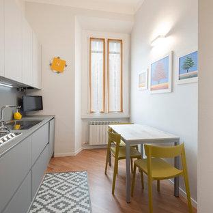 Foto di una cucina lineare contemporanea con ante lisce, ante grigie, pavimento in legno massello medio, nessuna isola, pavimento marrone e top grigio