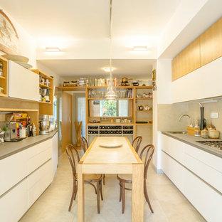 Immagine di una cucina contemporanea con ante lisce, ante bianche, top grigio, lavello da incasso, paraspruzzi beige, elettrodomestici bianchi e pavimento beige