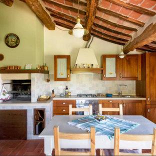 他の地域の大きい地中海スタイルのおしゃれなキッチン (ドロップインシンク、濃色木目調キャビネット、ラミネートカウンター、シルバーの調理設備、テラコッタタイルの床、赤い床) の写真