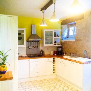 他の地域の広いコンテンポラリースタイルのおしゃれなキッチン (エプロンフロントシンク、白いキャビネット、ラミネートカウンター、白いキッチンパネル、セラミックタイルのキッチンパネル、シルバーの調理設備、セラミックタイルの床、マルチカラーの床) の写真