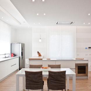 Idee per una cucina contemporanea di medie dimensioni con lavello da incasso, ante lisce, ante bianche, elettrodomestici in acciaio inossidabile, pavimento in legno massello medio, pavimento beige e top bianco