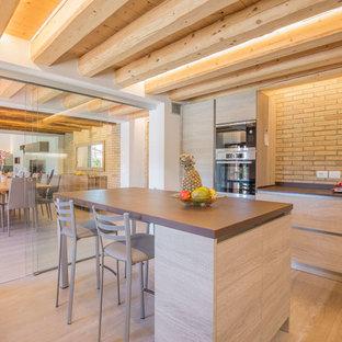 Idee per una grande cucina ad ambiente unico mediterranea con isola, ante lisce, ante in legno chiaro, paraspruzzi in mattoni, parquet chiaro, pavimento beige e top marrone
