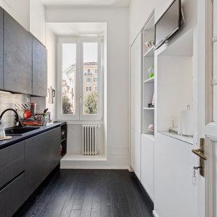 Ispirazione per una cucina parallela minimal chiusa e di medie dimensioni con lavello da incasso, ante lisce, ante nere, paraspruzzi grigio, paraspruzzi con piastrelle di cemento, elettrodomestici da incasso, nessuna isola, pavimento nero e top nero