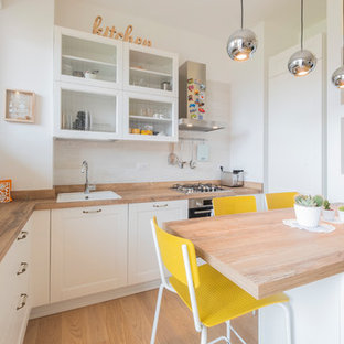 Scandinavian l-shaped kitchen in Milan with a drop-in sink, raised-panel cabinets, white cabinets, wood benchtops, white splashback, medium hardwood floors, a peninsula, brown floor and brown benchtop.