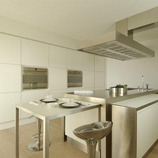 Foto di una cucina parallela minimalista con lavello sottopiano, ante lisce, ante bianche, top in acciaio inossidabile, parquet chiaro, isola, pavimento beige e top grigio