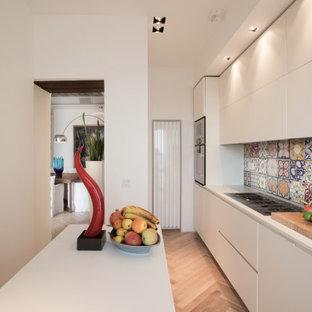 Foto di una piccola cucina lineare mediterranea chiusa con lavello integrato, ante lisce, ante bianche, top in superficie solida, paraspruzzi multicolore, paraspruzzi con piastrelle in ceramica, elettrodomestici in acciaio inossidabile, parquet chiaro, isola, pavimento giallo e top bianco