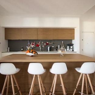 Esempio di una cucina minimal con ante lisce, ante marroni, paraspruzzi grigio, isola e pavimento marrone