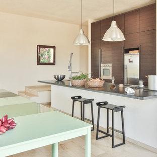 Foto di una cucina parallela design con ante lisce, ante in legno bruno, isola, pavimento beige e top grigio